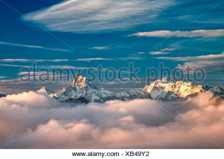 The morning fog of an autumn morning trying to conceal the majesty of the Matterhorn, Dent d'Herens and Weisshorn  - Alps, Aosta valley, Italy Europe - Stock Photo