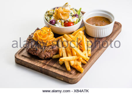 Wild steak with braised onions, French fries and a small salad - Stock Photo