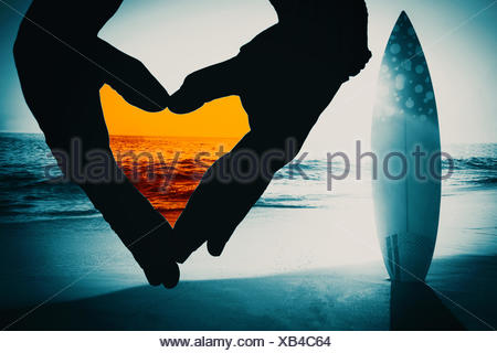 Composite image of close up of hands forming heart - Stock Photo