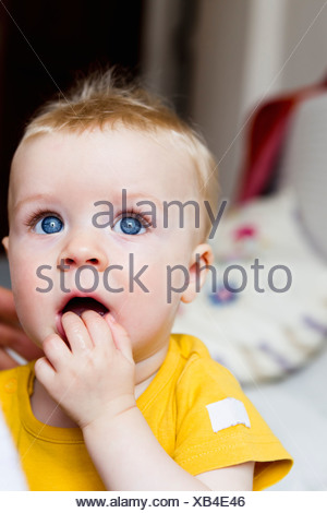 Close up of baby chewing fingers - Stock Photo