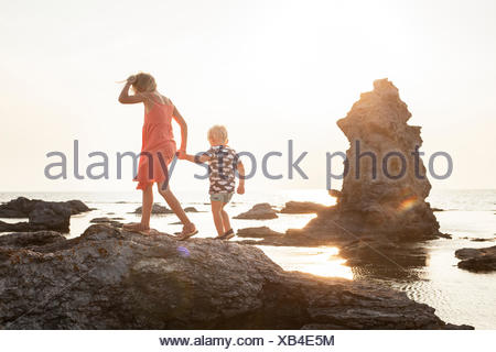 Sweden, Gotland, Faro, Gamle hamn, Girl (8-9) walking with brother (2-3) on coastal rocks - Stock Photo
