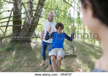 Father pushing son on tree swing in rural yard - Stock Photo