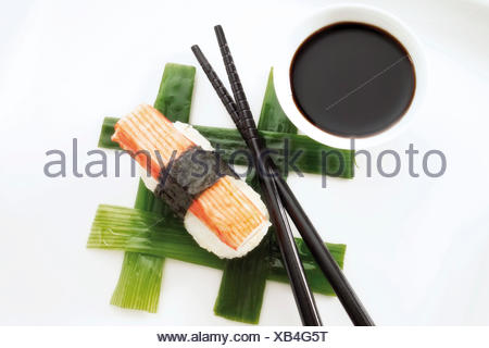 Sushi Nigiri, made with imitation crab meat and rice wrapped in nori seaweed and placed beside black chopsticks and a bowl of - Stock Photo