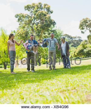 Happy extended family walking in park - Stock Photo