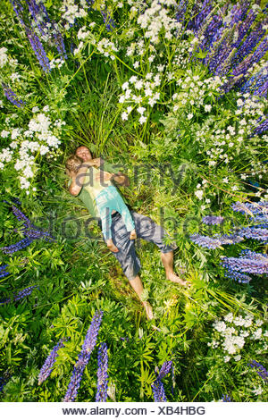 Finland, Man and girl (2-3) lying in meadow - Stock Photo