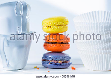 Stack of three colourful macarons, paper cups and two enamel cups - Stock Photo