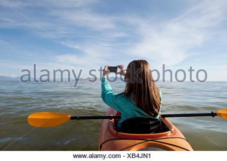 Rear view of young woman in kayak taking photograph, Great Salt Lake, Utah, USA - Stock Photo