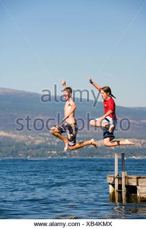 Teenagers jumping off a dock into Okanagan lake, British Columbia, Canada. - Stock Photo