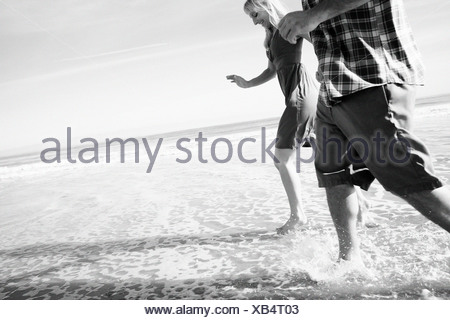 Couple run by the water and get their feet wet at the beach. - Stock Photo