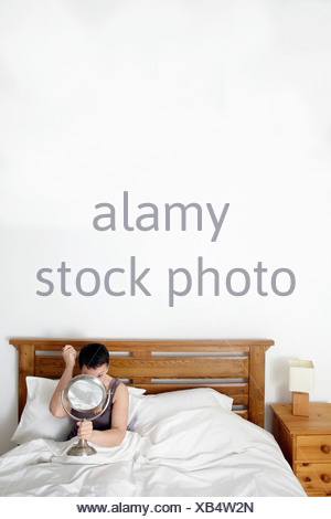 Woman in bed, looking in mirror - Stock Photo
