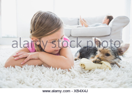 Little girl lying on rug with yorkshire terrier - Stock Photo