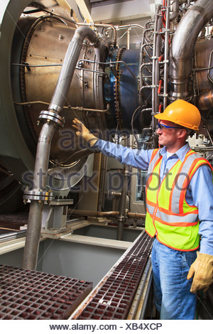 Engineer at fuel ignition stage of gas turbine which drives generators in power plant while turbine is powered down - Stock Photo