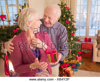 Man surprising woman with Christmas gift - Stock Photo