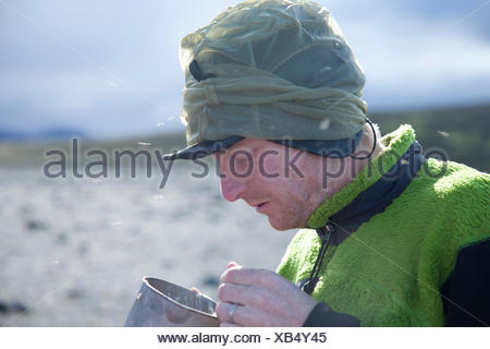 Young man eating breakfeast while camping - Stock Photo
