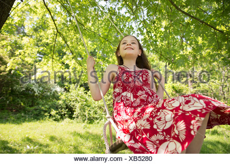 Summer. A girl in a sundress on a swing suspending from the branches of a tree. - Stock Photo