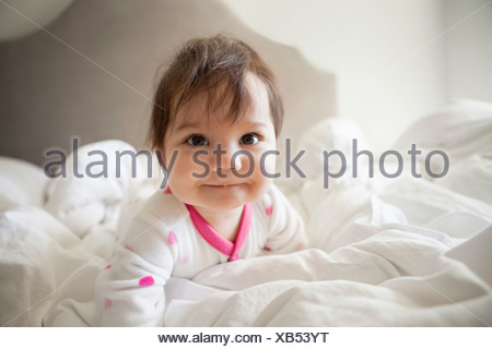 Baby girl crawling in bedsheets - Stock Photo