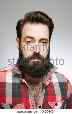 Studio portrait of aloof bearded young man - Stock Photo