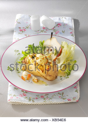 Au gratin potatoes with a pear and salad on a plate with a floral napkin and salt and pepper shakers - Stock Photo