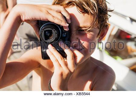 Sweden, Uppland, Runmaro, Barrskar, Portrait of boy (6-7) photographing - Stock Photo