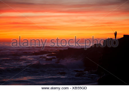 A lone fisherman at sunset. - Stock Photo