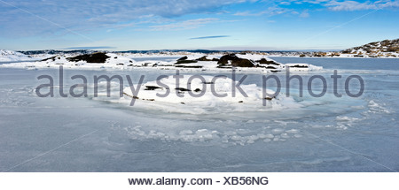 Panoramic shot of peaceful and calm frozen lake against the sky - Stock Photo