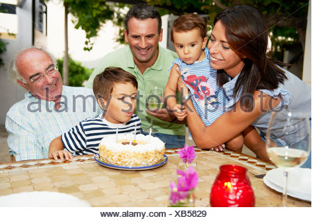 Family blowing candles out on cake - Stock Photo
