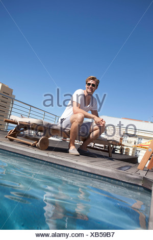 Man sitting by swimming pool - Stock Photo