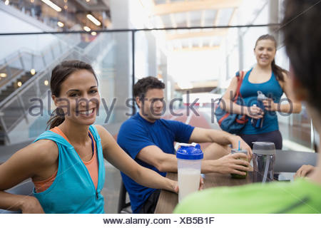 Portrait smiling woman drinking protein shake with friends - Stock Photo
