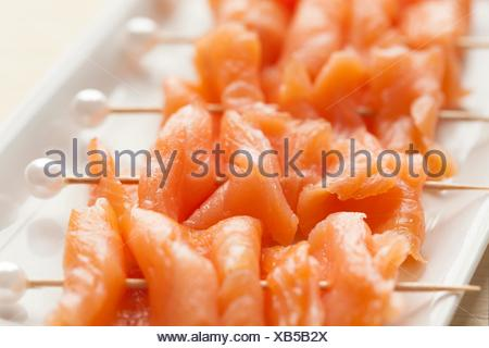 Smoked salmon on cocktail picks with a pearl as a festive snack. - Stock Photo