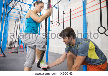 Instructor assisting woman in rope climb - Stock Photo