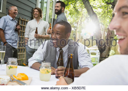Friends drinking beer at garden party lunch - Stock Photo