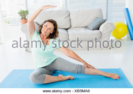 Mature woman stretching on exercise mat - Stock Photo