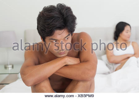 Couple not talking after argument in bed - Stock Photo