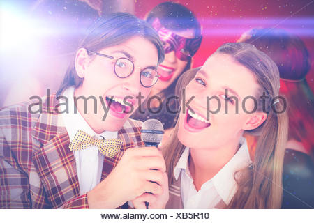 Composite image of happy geeky hipsters singing with microphone - Stock Photo