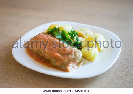 Meat-stuffed cabbage and potatoes on a plate on a table. - Stock Photo