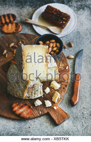 Cheese platter with cheese assortment, nuts, honey and bread on rustic wooden board over grey concrete background, selective focus. Party or gathering - Stock Photo