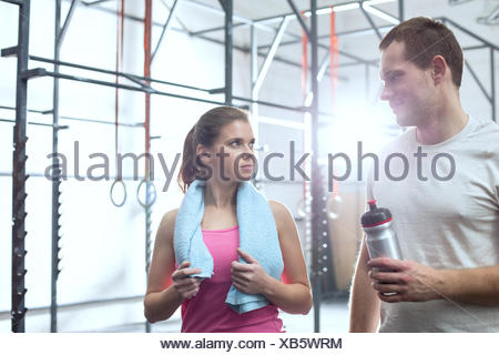 Man and woman looking at each other in crossfit gym - Stock Photo