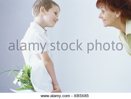 Boy surprising grandmother with bouquet of flowers - Stock Photo