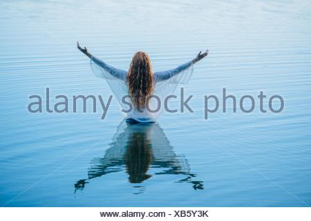 Rear view of young woman standing in blue lake with arms open - Stock Photo