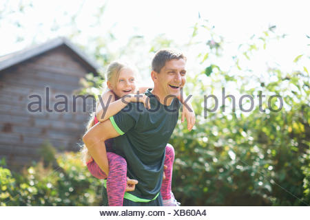 Father giving daughter piggyback in garden - Stock Photo