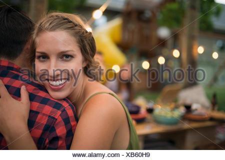 Portrait smiling girlfriend hugging boyfriend - Stock Photo