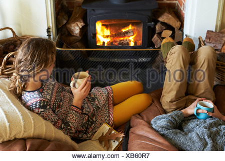 Children drinking cups of tea by fire - Stock Photo
