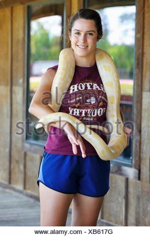 young woman posing with an Albinos Burmese python at Gator Country Wildlife Adventure Park, Beaumont, Texas, United States of America, North America. - Stock Photo