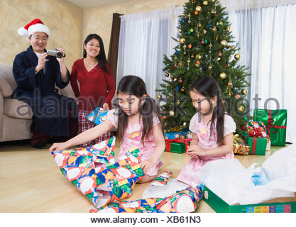 Father video taping Asian daughters opening Christmas presents - Stock Photo