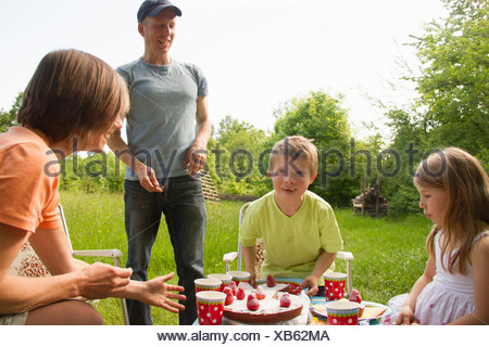 Family outdoors having birthday picnic - Stock Photo