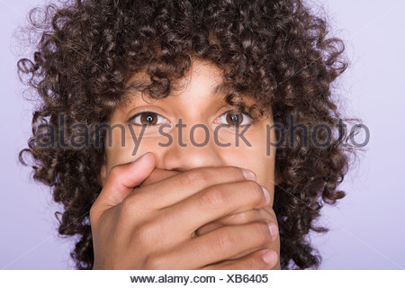 Portrait of teenage boy (14-15) covering mouth with hands - Stock Photo