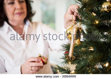Senior woman decorating Christmas tree - Stock Photo