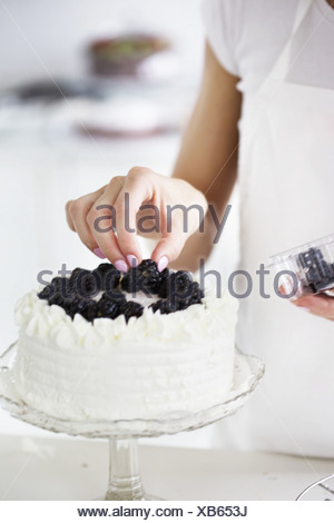 Woman decorating cake with fresh blackberries - Stock Photo