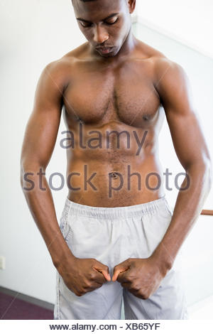 Shirtless muscular man shouting while flexing muscles - Stock Photo