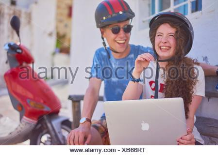 break at road trip with scooter: happy young English woman using mobile laptop while sitting next to attractive Dutch man - Stock Photo